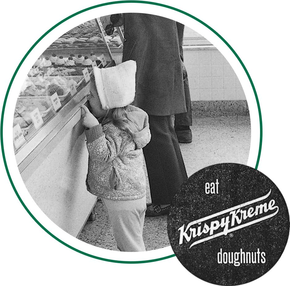 Child looking at doughnuts and Eat Krispy Kreme Doughnuts sign